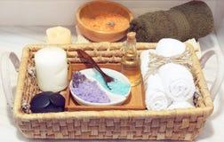 与一个集合的柳条筐温泉治疗的,多彩多姿的盐、芳香油、石头、蜡烛和软的毛巾,在一个白色选项旁边 免版税库存图片