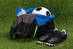 与一个集合的蓝色袋子踢的在绿草的橄榄球 库存照片