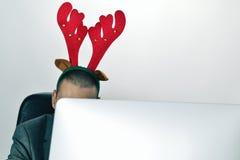与一个驯鹿鹿角头饰带的商人在他的办公室 库存图片