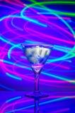 与一个鸡尾酒的玻璃与反对抽象照明背景的冰  免版税库存照片