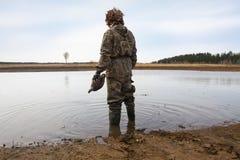 与一个鸭子诱饵的猎人在他的在岸的手立场 免版税库存图片