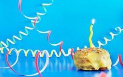与一个黄色灼烧的蜡烛的生日杯形蛋糕在与彩纸带的生动的蓝色背景 库存照片