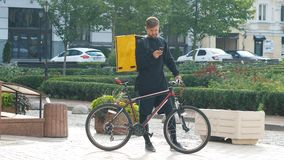 与一个黄色袋子和自行车的一位传讯者寻找在电话的客户的地址 有a的年轻送货人 股票视频