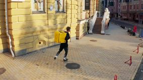 与一个黄色袋子的一位传讯者在城市街道上滑冰 有一个背包的一个人在溜冰鞋 送货服务工作者 影视素材