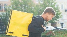 与一个黄色袋子的滑稽的传讯者跳舞 有背包的一个有胡子的人无所事事  送货服务工作者 股票录像