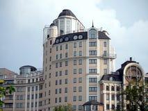与一个黑屋顶的一个现代高多层的大厦反对多云灰色天空 免版税库存照片