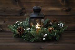 与一个黑灯笼的装饰的出现花圈有灼烧的茶光的和门户开放主义在木背景 库存图片