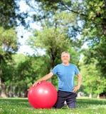 与一个锻炼球的成熟男性在公园 免版税库存照片