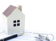 与一个建筑模型的租赁协议联络和计算器和笔和钥匙没有商标或商标 免版税库存照片