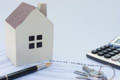 与一个建筑模型的租赁协议联络和计算器和笔和钥匙 免版税库存照片
