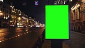 与一个绿色屏幕的一个广告牌在一条繁忙的夜街道上 股票录像