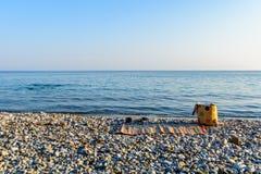 与一个黄色袋子的旅行背景,在一个美丽的海滩的沙子在一个晴朗的夏日 免版税库存图片
