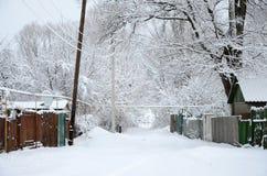 与一些老房子和用雪厚实的层数盖的一条宽广的高速公路的一个土气冬天风景  库存照片