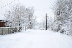 与一些老房子和用雪厚实的层数盖的一条宽广的高速公路的一个土气冬天风景  免版税库存图片