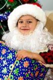 与一件礼物的小的圣诞老人在他的在圣诞树的背景的手上 免版税图库摄影