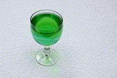 与一份绿色饮料的一块美丽的玻璃灰色表面上 库存照片