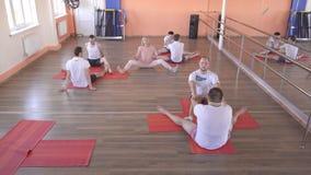 与一位单独辅导员的瑜伽班有一个美丽的白种人女孩的在一现代健身俱乐部,男性朋友 股票视频