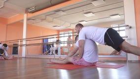 与一位单独辅导员的瑜伽班有一个美丽的白种人女孩的在一现代健身俱乐部,男性朋友 股票录像