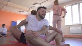 与一位单独辅导员的瑜伽班有一个美丽的白种人女孩的在一现代健身俱乐部,男性朋友 影视素材