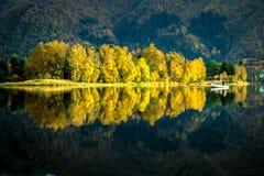 与一位孤立渔夫的美好的风景白色小船、五颜六色的树、山和湖反射的在秋天 免版税库存图片