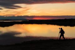 与一位摄影师的剪影的日落Myvatn的冰岛 库存图片