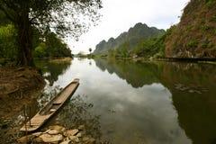 与一位木渔夫的小船的平静的湖风景 免版税库存照片