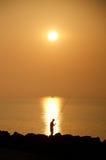 与一位渔夫和一艘小驳船的日出在天际,考尔莱,意大利 库存照片