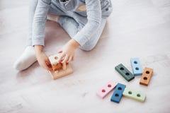 与一位玩具设计师的儿童游戏在儿童` s屋子的地板上 阻拦演奏影子二白色的五颜六色的查出的孩子 免版税库存图片