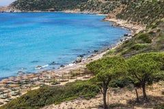 与一切的一个天堂海滩在一个梦想假日需要:绿松石海、金黄沙子、秸杆遮光罩伞和杉树, 库存照片
