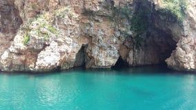 与一加深的石岩石在天蓝色的海 库存照片