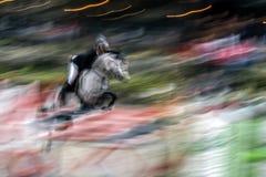 与一匹移动的车手和马的抽象图象在展示跳跃 库存照片