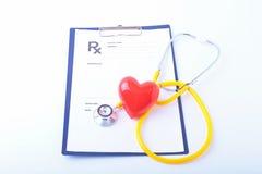与一医疗听诊器rx preascription的心脏,隔绝在木背景 免版税库存图片