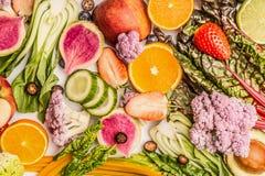 与一半的五颜六色的水果和蔬菜背景桔子和莓果,顶视图 免版税图库摄影