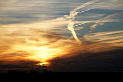 与一只多云鸟的美好的红金黄日落 免版税库存照片