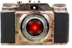 与一只红色透镜眼睛的老生锈的照相机 免版税库存图片