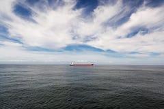 与一只红色货船的海景 图库摄影