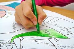 与一只绿色蜡笔的女孩图画在教室 免版税图库摄影