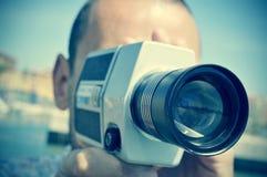 与一台减速火箭的影片照相机的年轻人摄制 免版税库存图片