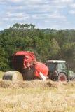 与一台圆的打包机的农夫打包用的干草 免版税库存图片