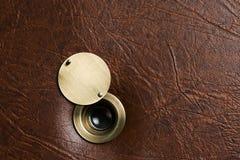 与一台开放制音器的窥视孔在一个棕色人造皮门 免版税库存图片