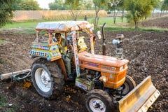 与一台拖拉机的一个农夫耕的领域在北旁遮普邦巴基斯坦 免版税库存图片
