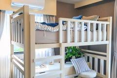 与一台枕头和空调器的一张木床在childre 免版税库存照片