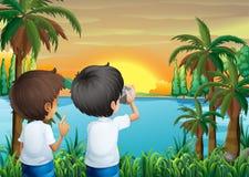 与一台照相机的两个孩子在河岸 免版税图库摄影