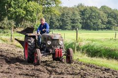 与一台老拖拉机的农夫骑马在荷兰农业节日期间 免版税库存照片