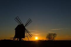 与一台老风车的剪影的日落 免版税库存图片
