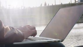与一台膝上型计算机的商人在公园 股票录像