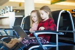 与一台膝上型计算机的孩子在机场,当等待他的飞行时 免版税库存图片