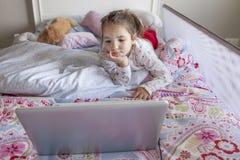 与一台膝上型计算机的小女孩观看的电影在床上 库存照片