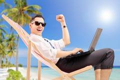 与一台膝上型计算机的愉快的商人在海滩 图库摄影
