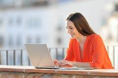 与一台膝上型计算机的愉快的自己经营的工作在阳台上 免版税库存照片